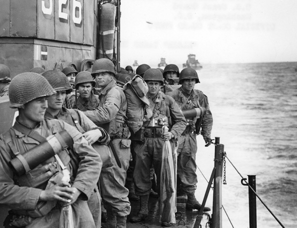 Photo of American soldiers onboard a ship approaching the coast of Normandy.